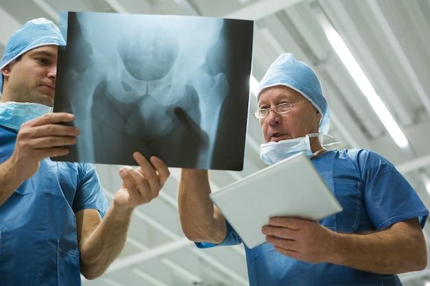 Chirurgiens masculins tenant une tablette numérique tout en discutant de la radiographie