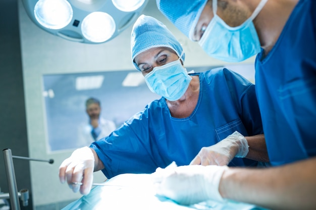 Les chirurgiens qui pratiquent l'exploitation en salle d'opération