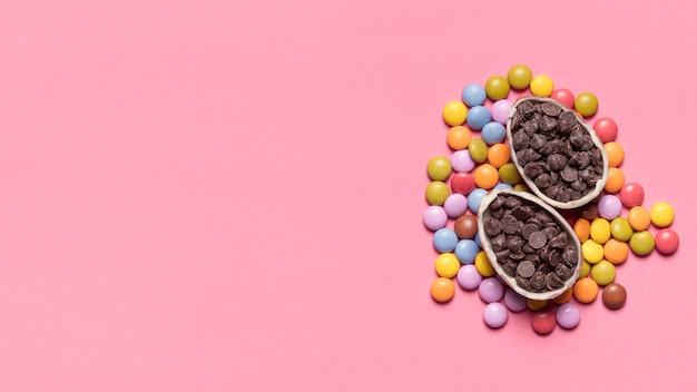 Choco chips remplies dans les oeufs de pâques sur des bonbons aux pierres précieuses sur fond rose