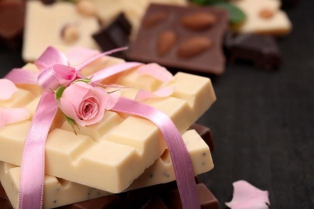 Chocolat attaché avec un ruban rose sur un mur noir