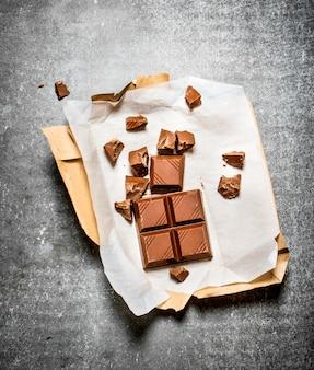 Chocolat au lait en papier. sur la table en pierre.