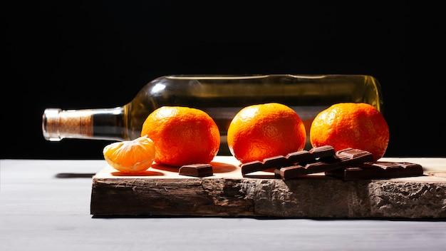 Chocolat aux mandarines et vin blanc sur fond sombre. dîner romantique. amour, romance. fruits et alcool le jour de la saint-valentin.