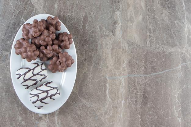 Chocolat aux noisettes et bonbons sur une assiette, sur le bleu.