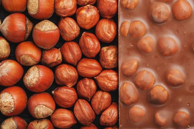 Chocolat aux noisettes, noix en coque sous forme de texture solide. chocolat au lait dessert aux noix, doux contraste.