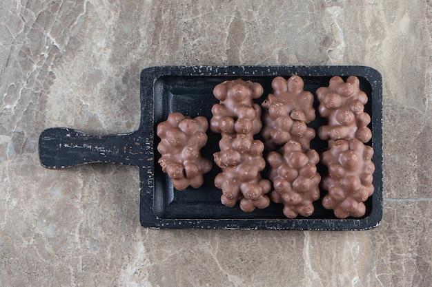 Chocolat aux noisettes sur une planche sur marbre.
