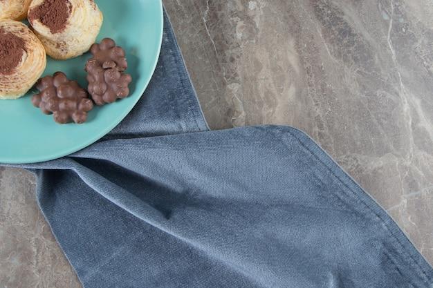 Chocolat aux noisettes et poudre de cacao sur les cookies sur une assiette sur une serviette sur bleu.