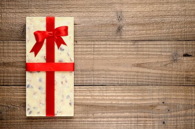 Chocolat blanc avec ruban sur fond en bois