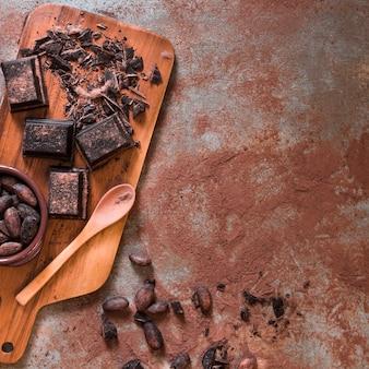 Chocolat cassé brisé et fèves de cacao sur toile de fond rustique