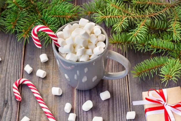 Chocolat chaud au café avec de la guimauve sur fond de table en bois rustique, boîtes de cadeau de bonbons cannes sapin