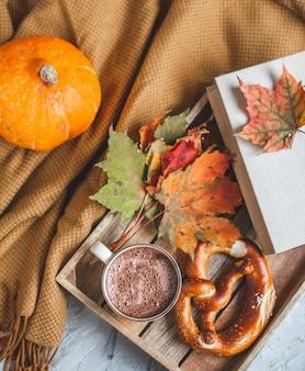Chocolat chaud automne temps boulangerie couverture de bretzel feuilles jaunes fond gris