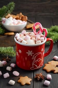 Chocolat chaud aux guimauves et épices sur un fond en bois foncé. composition de noël