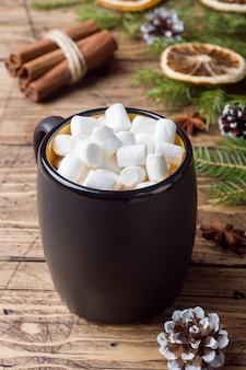 Chocolat chaud avec des bâtons de cannelle à la guimauve, anis, noix sur bois