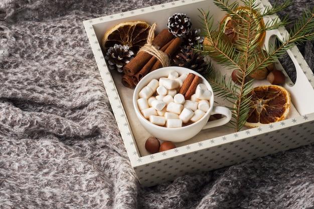 Chocolat chaud avec des bâtons de cannelle à la guimauve, anis, noix sur un plateau en bois