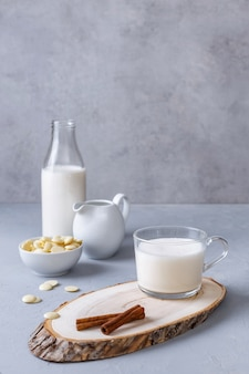 Chocolat chaud blanc et cannelle sur un support en bois sur une surface grise. concept de petit déjeuner sain. boissons céto. copiez l'espace.