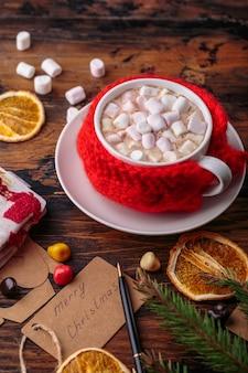 Chocolat chaud cacao avec guimauves tricoté à la main tissu rouge pour une tasse