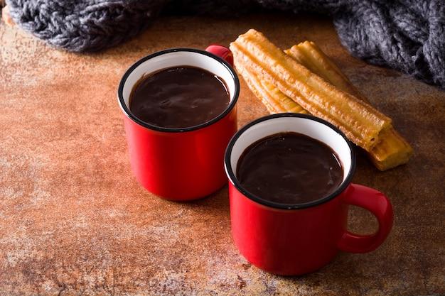 Chocolat chaud avec des churros sur une surface rouillée