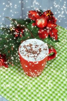 Chocolat chaud à la crème dans une tasse de couleur, sur une serviette, sur fond de décorations de noël