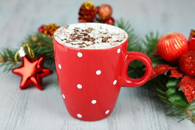 Chocolat chaud à la crème dans une tasse de couleur, sur table, sur fond de décorations de noël