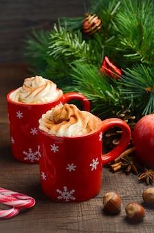 Chocolat chaud à la crème fouettée dans des tasses rouges. composition de noël