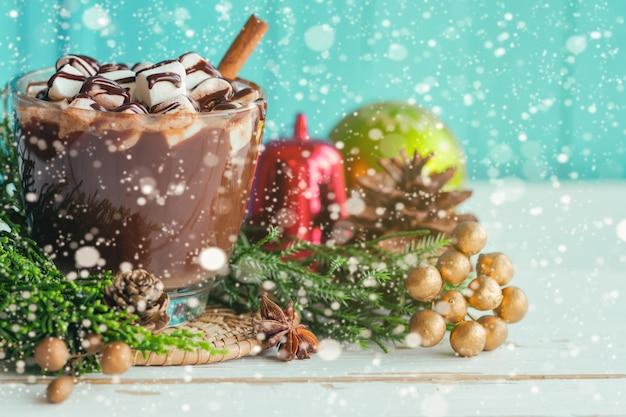 Chocolat chaud dans une garniture en verre avec une sauce à la guimauve et au chocolat sur le thème de noël.