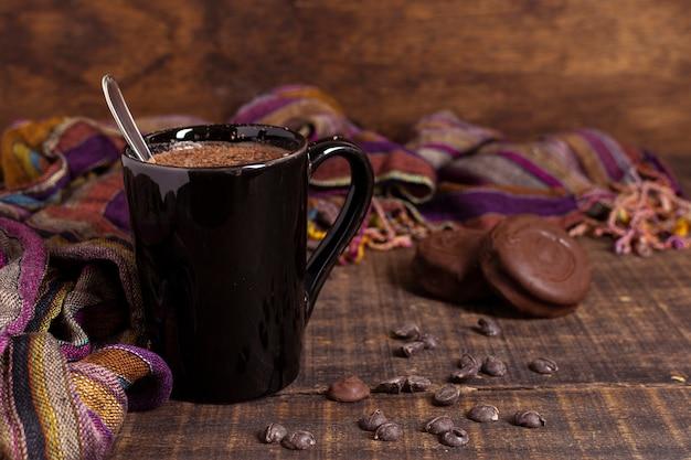 Chocolat chaud dans une tasse avec des biscuits et des chips de cacao