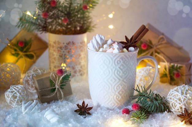 Chocolat chaud dans une tasse blanche avec des guimauves et des cadeaux de noël sous la lumière vive. boisson de noël.
