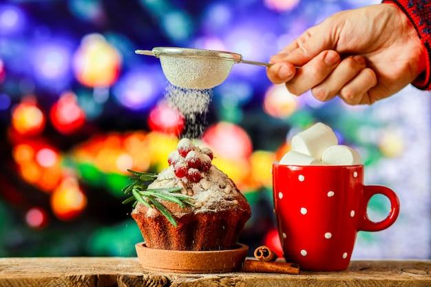 Chocolat chaud sur fond d'arbre de noël avec un petit gâteau de noëlbonbons pour le nouvel an
