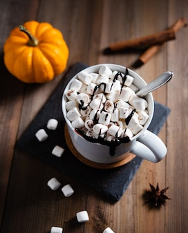 Chocolat chaud avec guimauve et cannelle dans une tasse blanche sur une table en bois. vue de dessus