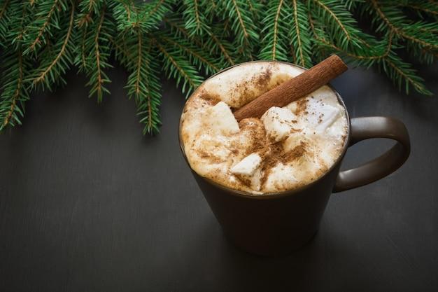 Chocolat chaud à la guimauve et à la cannelle sur le noir avec une branche d'arbre de noël.