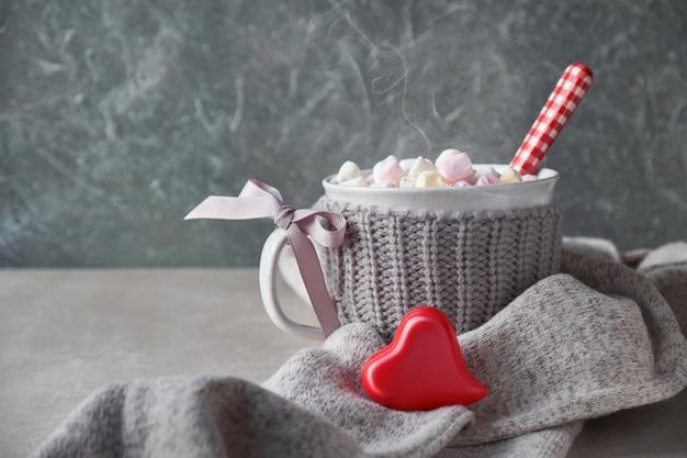 Chocolat chaud avec des guimauves, coeur rouge sur la tasse sur la pierre grise