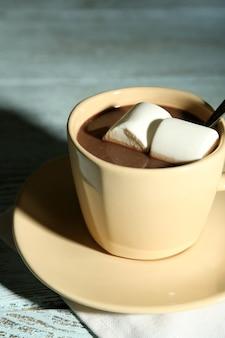 Chocolat chaud avec des guimauves dans une tasse, sur fond de bois