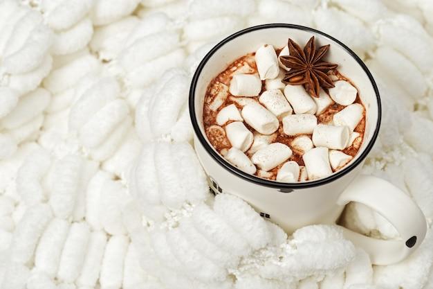 Chocolat chaud avec des guimauves avec un tricot doux et confortable