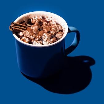 Chocolat chaud de noël dans une tasse bleue sur fond bleu en lumière dure.
