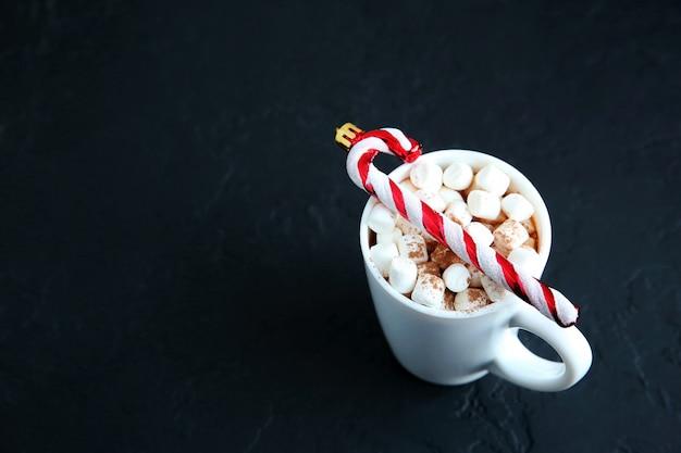Chocolat chaud de noël avec des guimauves, une canne en bonbon à la menthe poivrée à la tasse, espace de copie.