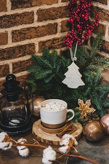 Chocolat chaud de noël avec mini guimauves dans une vieille tasse en céramique avec des bougies sur un bois.