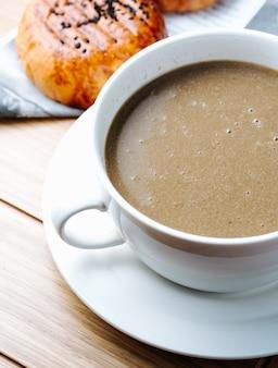Chocolat chaud servi avec des petits pains fraîchement cuits