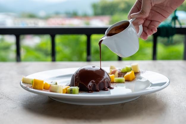 Chocolat chaud versé sur un dôme de cacao avec des tranches de fruits
