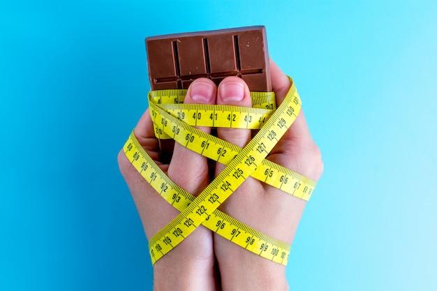 Chocolat dans les mains attachées avec du ruban à mesurer jaune