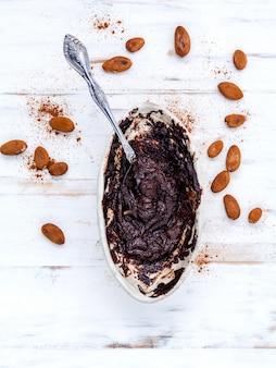 Chocolat fondu avec des fèves de cacao rôties sur une table blanche.