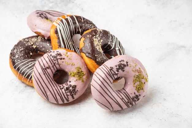 Chocolat glacé et beignets roses sur une surface en marbre.