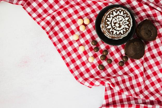 Chocolat; muffins et biscuits sur une serviette rouge à carreaux sur fond blanc