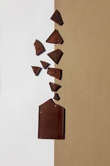Chocolat noir coupé sur fond blanc et marron. vue ci-dessus