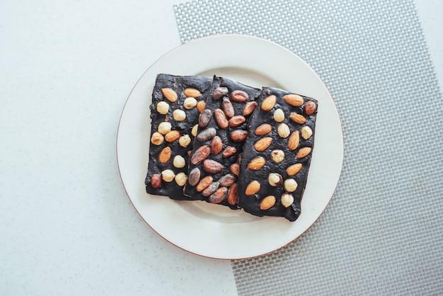 Chocolat noir, isolé sur blanc avec des noix entières.