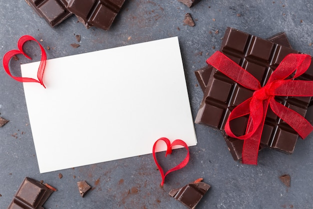 Chocolat noué avec un ruban rouge et une carte de voeux vierge