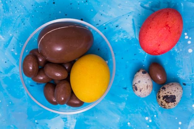 Chocolat et oeufs de pâques colorés sur la table
