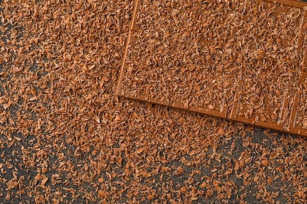 Chocolat râpé avec barre de choco à plat sur un fond sombre