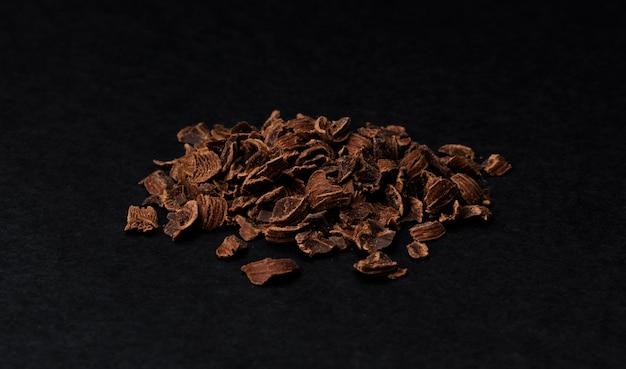 Chocolat râpé. tas de chocolat moulu isolé sur fond noir, gros plan