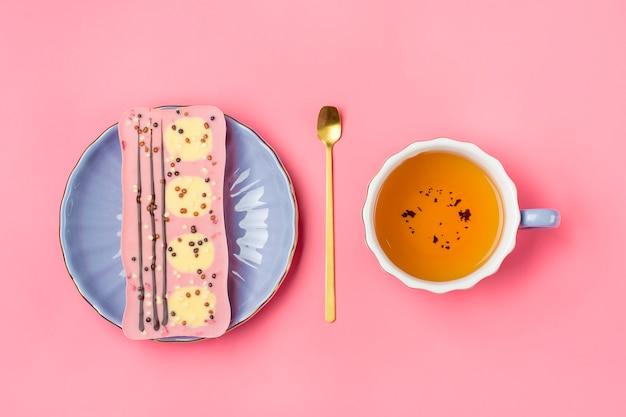 Chocolat rose aux raisins secs et noix sur plaque lilas, tasse de thé noir, cuillère dorée sur rose