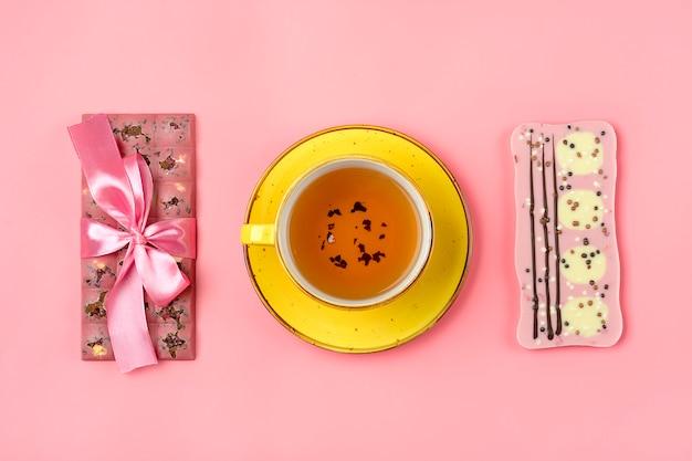 Chocolat rose aux raisins secs et noix, tasse jaune de thé noir sur fond rose dessert time