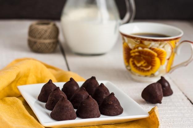 Chocolats aux truffes avec une tasse de café et de crème sur un fond blanc